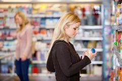 Il prodotto della giovane donna confronta Immagine Stock