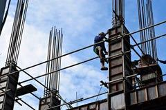 Il produttore d'acciaio filippino della costruzione che scende facendo uso dell'armatura convoglia su grattacielo Immagine Stock Libera da Diritti