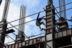 Il produttore d'acciaio filippino della costruzione che scende facendo uso dell'armatura convoglia su grattacielo Immagini Stock Libere da Diritti