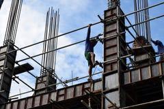 Il produttore d'acciaio filippino della costruzione che scende facendo uso dell'armatura convoglia su grattacielo Fotografie Stock
