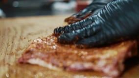 Il professionista applica i condimenti sul pezzo di carne in cucina in ristorante video d archivio