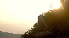 Il professionista di yoga fa in avanti il piegamento sul movimento lento della roccia stock footage