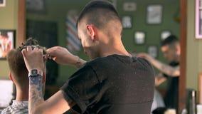 Il professionista ha tatuato il barbiere che dà un nuovo taglio di capelli al suo cliente in un parrucchiere archivi video