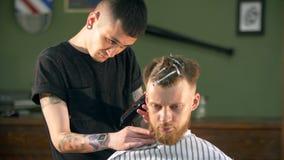 Il professionista ha tatuato il barbiere che dà un nuovo taglio di capelli al suo cliente in un parrucchiere stock footage
