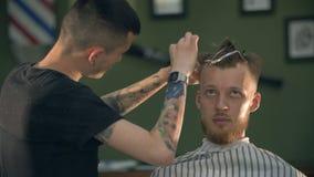 Il professionista ha tatuato il barbiere che dà un nuovo taglio di capelli al suo cliente in un parrucchiere video d archivio