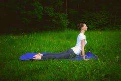 Il profilo di bella giovane donna sorridente che risolve sulla stuoia blu in vicolo del parco, facente l'allungamento si esercita Fotografia Stock