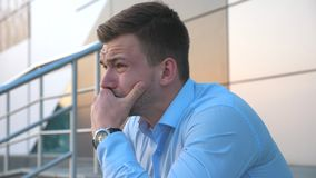 Il profilo di giovane uomo d'affari disperato che parla sullo Smart Phone e che si siede sulle scale si avvicina all'edificio per video d archivio