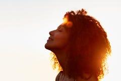 Il profilo di una donna con l'afro silhoutted contro il sole di sera Immagini Stock Libere da Diritti