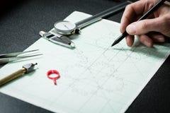 Il progettista dei gioielli lavora ad uno schizzo del disegno della mano Fotografia Stock