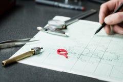 Il progettista dei gioielli lavora ad uno sketc del disegno della mano Fotografia Stock Libera da Diritti