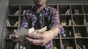 Il progettista del giovane monta manualmente la piccola scatola di cartone d'imballaggio per i prodotti Fotografie Stock Libere da Diritti