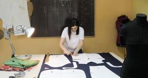Il progettista dell'abbigliamento sta lavorando con le misure su una tavola dello studio stock footage