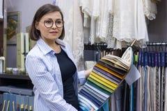 Il progettista femminile, il decoratore interno, proprietario di deposito mostra il tessuto Negozio del tessuto di piccola impres Fotografia Stock