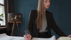 Il progettista femminile in ufficio che lavora agli architetti proietta stock footage
