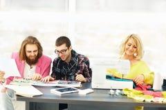 Il progettista moderno ed il suo gruppo fanno i disegni di modo nel creativ Immagini Stock