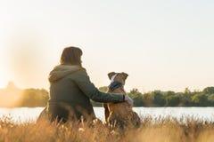 Il proprietario del cane ed il suo animale domestico si siedono alla riva al tramonto immagine stock