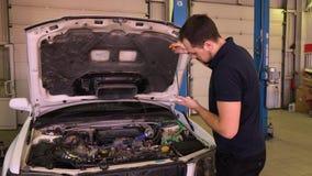 Il proprietario dell'automobile controlla l'asta misura-livello dell'olio in garage video d archivio