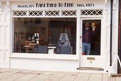 Il proprietario di negozio che aprono l'annotazione, il CD e l'alta fedeltà comperano Fotografia Stock
