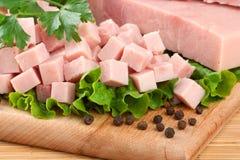 Il prosciutto del porco ha organizzato sulla scheda di taglio con prezzemolo a Fotografia Stock