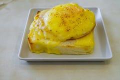 Il prosciutto ed il formaggio hanno farcito il pane inzuppato in latte/uova e zucchero e fritto in padella sulla tavola bianca Fotografia Stock