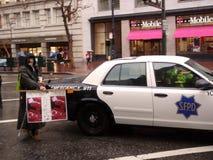 Il protestatore tiene il segno davanti all'automobile di SFPD Fotografia Stock Libera da Diritti