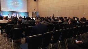 Il pubblico ascolta gli altoparlanti alla sala per conferenze stock footage