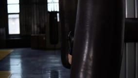Il pugile bello perfora la borsa pesante mentre indossa i guanti neri Sport, fondo del ring Movimento lento stock footage