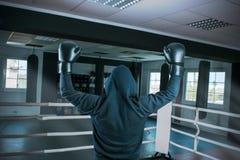 Il pugile maschio in un anello di sport ha sollevato due mani gloved sopra la sua testa in un gesto di conquista immagine stock