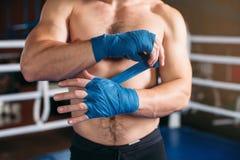 Il pugile tira la fasciatura prima della lotta o dell'addestramento Immagine Stock