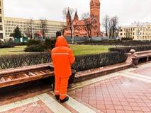Il pulitore di lavoro maschio in camici arancio che indossano il lavoro dei vestiti dell'abito pulisce le vie della città immagini stock