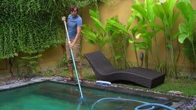 Il pulitore professionale della piscina del giovane fa il servizio di pulizia dello stagno archivi video
