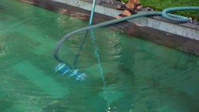 Il pulitore professionale della piscina del giovane fa il servizio di pulizia dello stagno video d archivio