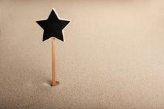 Il puntatore, annunci imbarca nella stella della forma nella sabbia Fotografia Stock Libera da Diritti