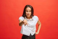 Il punto arrogante della donna di affari e vi volete, mezzo ritratto del primo piano di lunghezza su fondo rosso Fotografie Stock Libere da Diritti