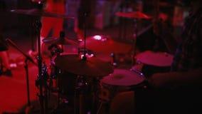 Il punto di vista del primo piano del batterista gioca in scena Banda rock di concerto in un night-club o in una promenade L'uomo video d archivio