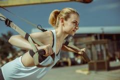 Il punto di vista del primo piano della donna che allegra fare spinge aumenta l'allenamento urbano per le armi Fotografia Stock