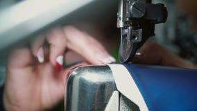 Il punto di vista del primo piano della donna s passa il lavoro alla fabbrica dell'indumento facendo uso della macchina per cucir stock footage