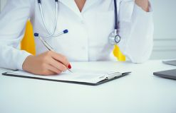 Il punto di vista del primo piano di medico femminile passa il modulo di iscrizione paziente di riempimento Sanità e concetto med fotografia stock