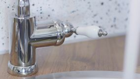 Il punto di vista del primo piano di qualcuno mano muove il rubinetto del rubinetto per aprirlo in modo dall'acqua potrebbe scorr video d archivio