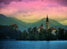 Il punto di vista del tramonto di Julian Alps, lago ha sanguinato con la chiesa della st Marys del presupposto sulla piccola isol Immagini Stock