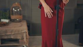 Il punto di vista del vocalist in vestito rosso con luminoso compone per eseguire al microfono ballo archivi video