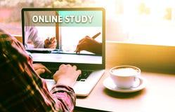 Il punto di vista della spalla e della parte posteriore dello studente che per mezzo del computer portatile con online impara Fotografie Stock