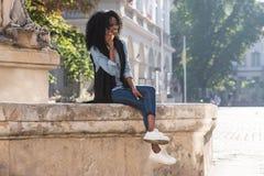 Il punto di vista orizzontale della ragazza afroamericana magnifica che si siede sulla fontana mentre parlando tramite telefono c immagini stock libere da diritti