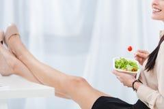 il punto di vista parziale della donna di affari con porta via l'alimento nel luogo di lavoro Fotografia Stock