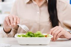 il punto di vista parziale della donna di affari con porta via l'alimento nel luogo di lavoro Fotografie Stock
