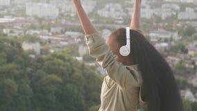 Il punto di vista posteriore di bella ragazza afroamericana ascolta musica e gode di Giovane ragazza nera sorridente sulla città  video d archivio