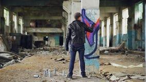 Il punto di vista posteriore del pittore dei graffiti che crea la bella immagine con l'interno della pittura dell'aerosol ha abba stock footage