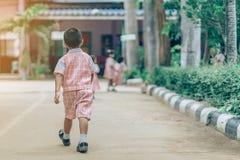Il punto di vista posteriore del ragazzo ha seguito le ragazze sulla via per andare all'aula fotografia stock libera da diritti