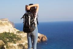 Il punto di vista posteriore del viaggiatore sta stando sulla roccia con lo zaino fotografia stock
