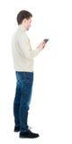 il punto di vista posteriore dell'uomo di affari utilizza il telefono cellulare immagini stock libere da diritti